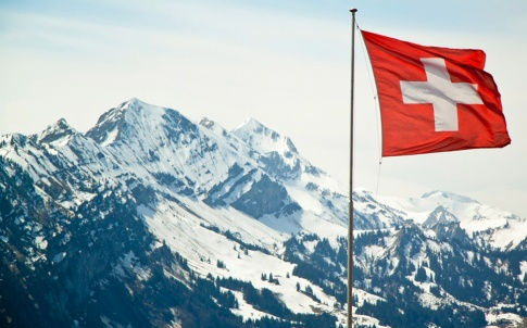 Flag of Switzerland on the Alps mountains landscape background.