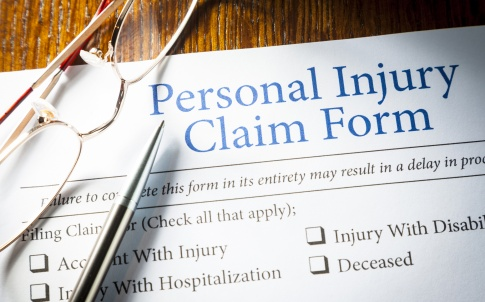 Personal Injury Claim form with pen and glasses