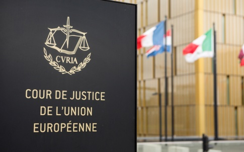 Sign of European Court of Justice in foreground, in the background is the building and European flags flying