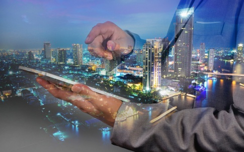 man in suit looking at laptop with city nightscape in the background