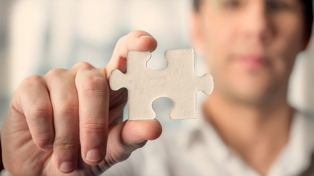 macro-puzzle-piece-hold-by-man