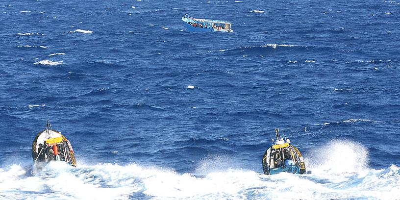 Människosmugglarna beblandar sig med migranterna för att  komma undan. Kustbevakningen fotar därför på avstånd för att dokumentera vem som kör båten. Foto: Kustbevakningen