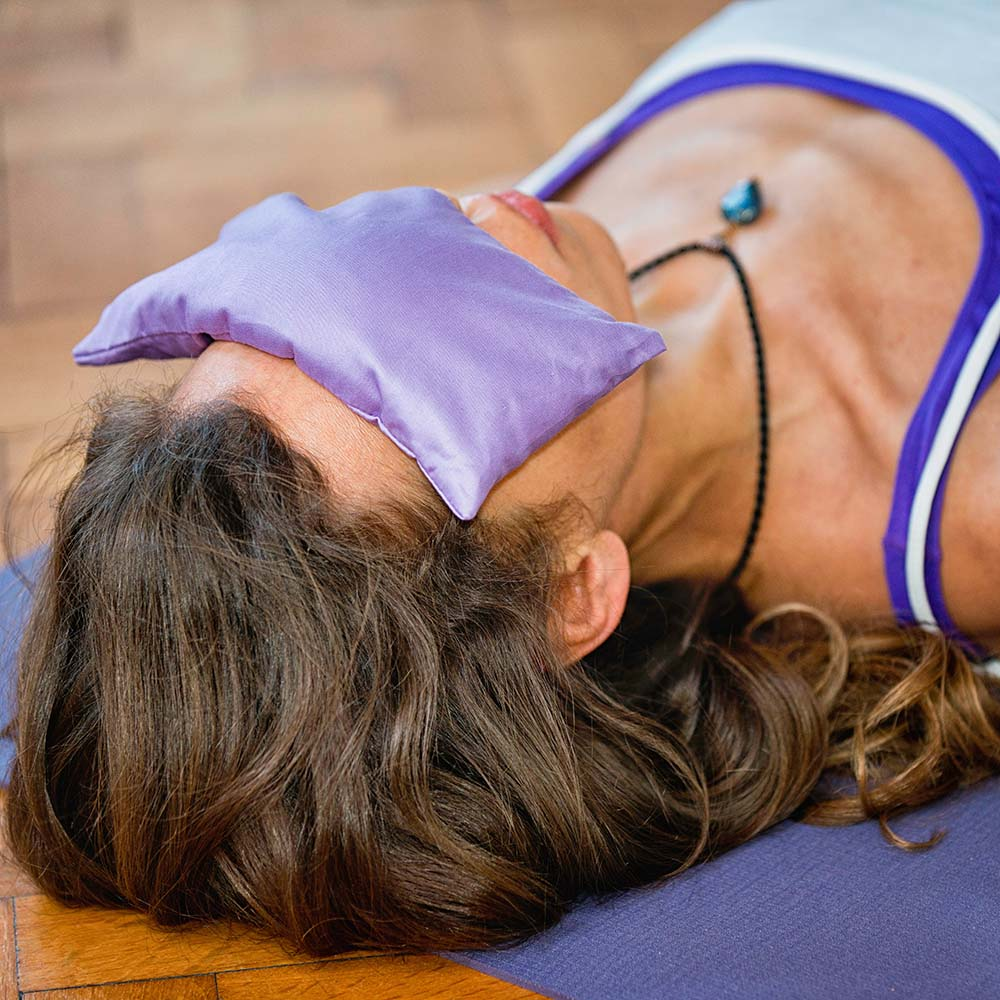 Yoga Savasana position with lavender eye pillow