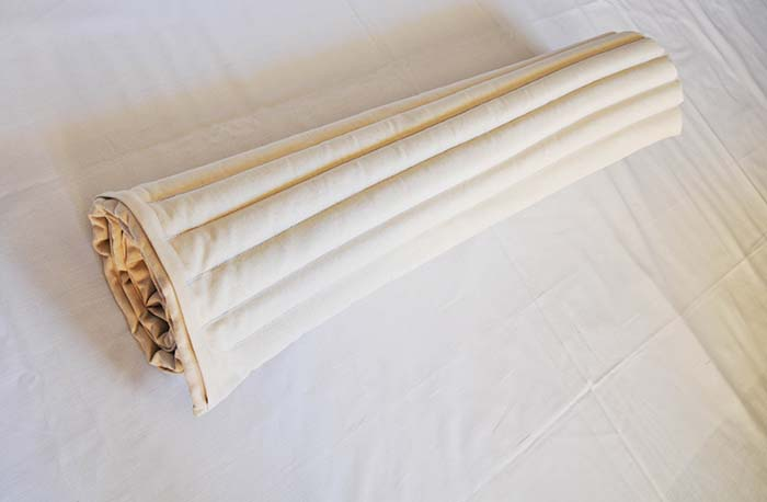 rolled up mustard seed mattress by EcoHealthLAB, easy to carry with