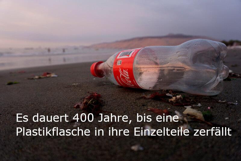 Zero Waste: Bild einer leeren Coca-Cola-Flasche am Strand zur Verdeutlichung der Halbwertszeit von Plastik