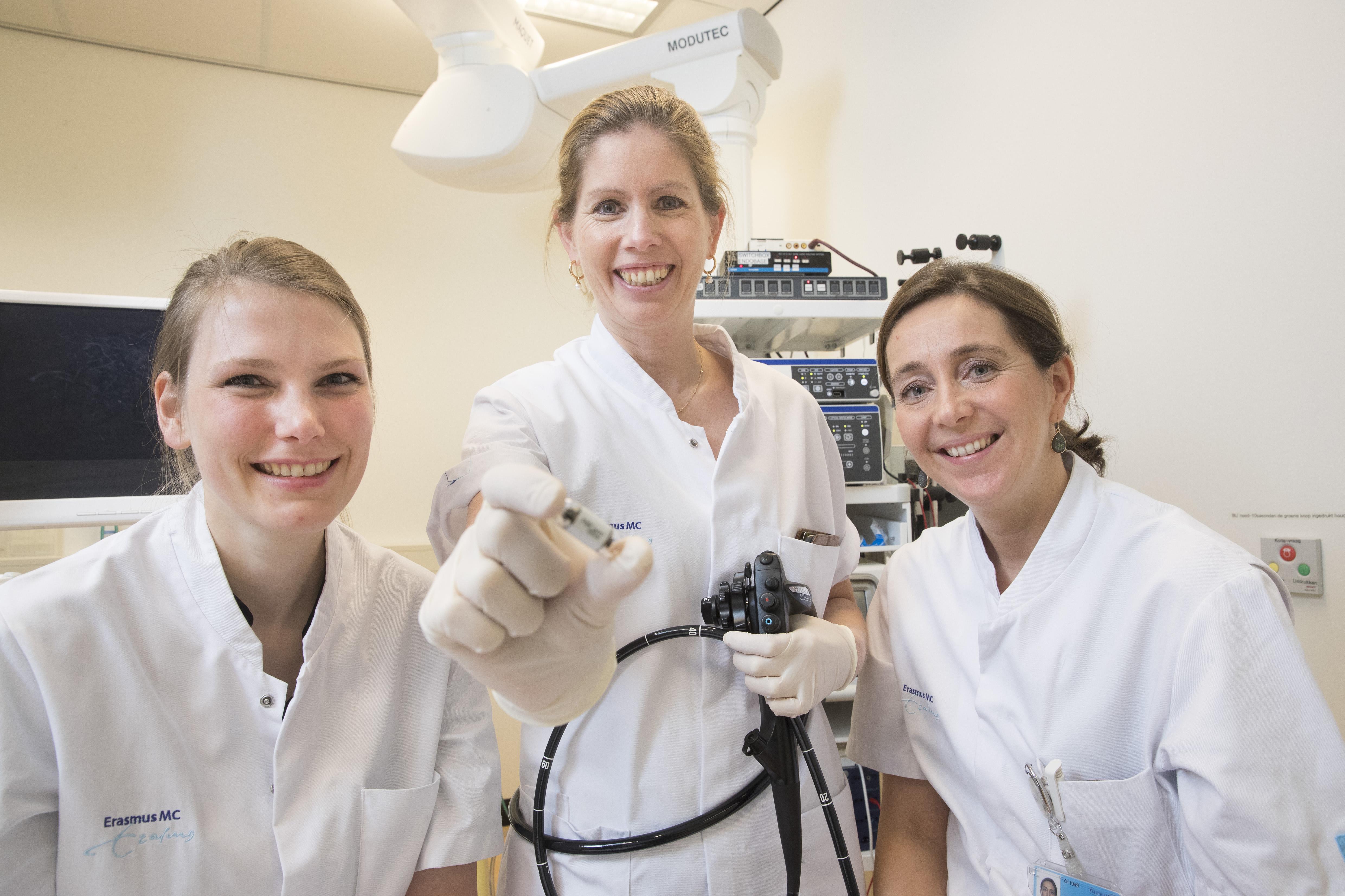 Maag-, Darm- en Leverarts dr. Manon Spaander met de camerapil, geflankeerd door arts-onderzoeker Fanny Vuik (links) en researchverpleegkundige Sophia van Baalen.