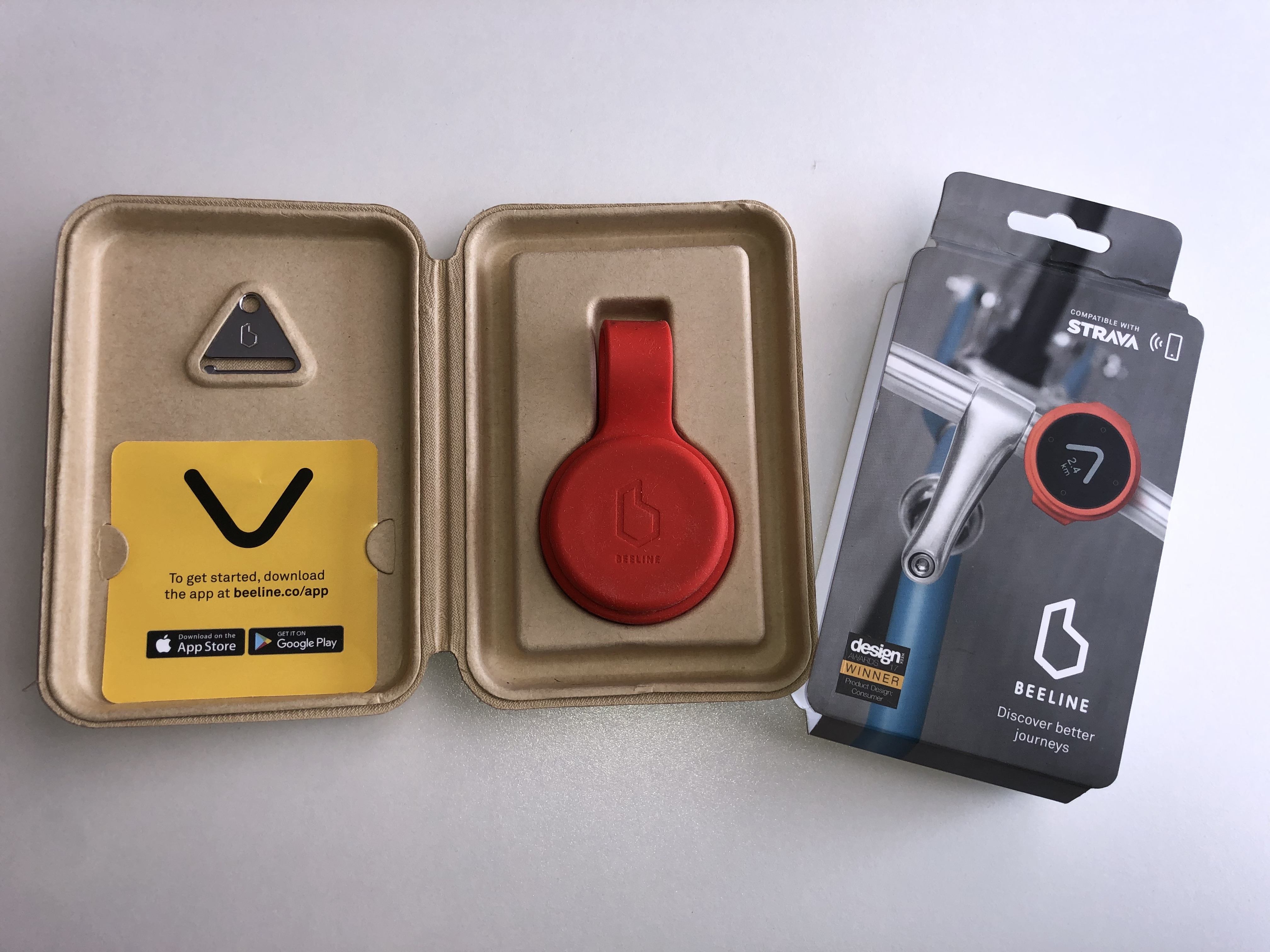 Opened red Beeline Velo box showing device, strap, box sleeve, keyring and instructions