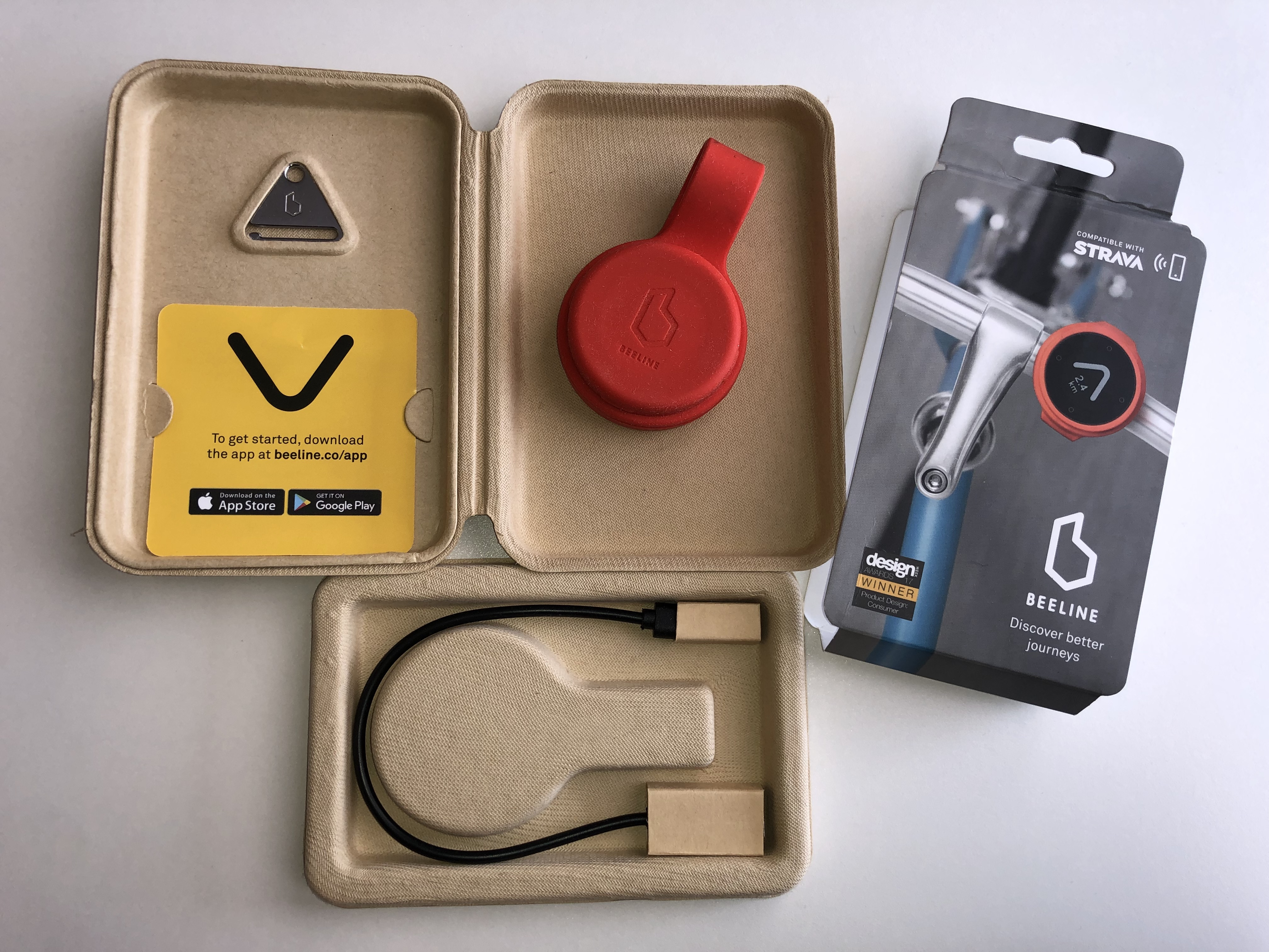 Opened Beeline Velo package in red. Shows device, keyring, instructions, box sleeve, charging cable.