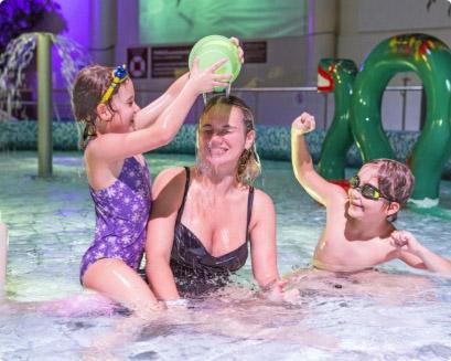Äiti ja lapset leikkimässä lastenaltaassa