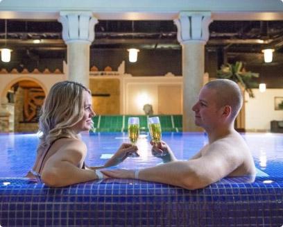 Pariskunta nauttimassa kuohuviiniä lämminvesialtaassa