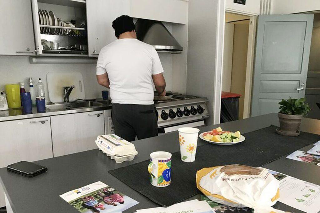 Kuvassa paperiton mies laittaa ruokaa Helsingin Diakonissalaitoksen päiväkeskuksessa.