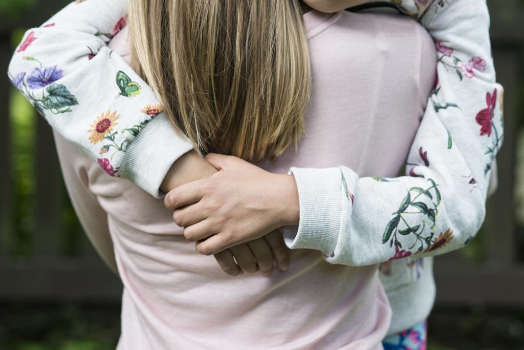 Kuvassa kaksi tyttöä halaavat toisiaan.