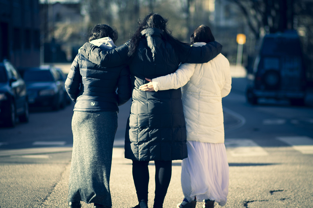 Kuvassa on kolme romanialaista romaninaista kävelemässä käsikynkkää kadulla.