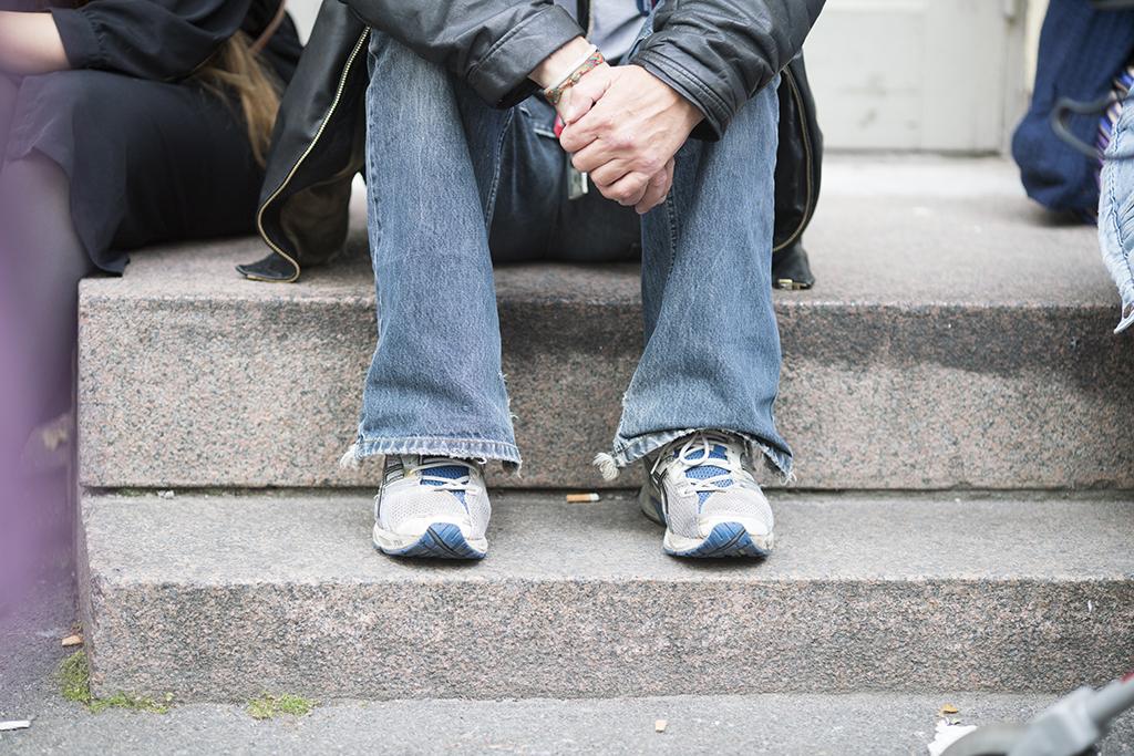 Kuvassa näkyy rappusilla istuvien ihmisten jalkoja