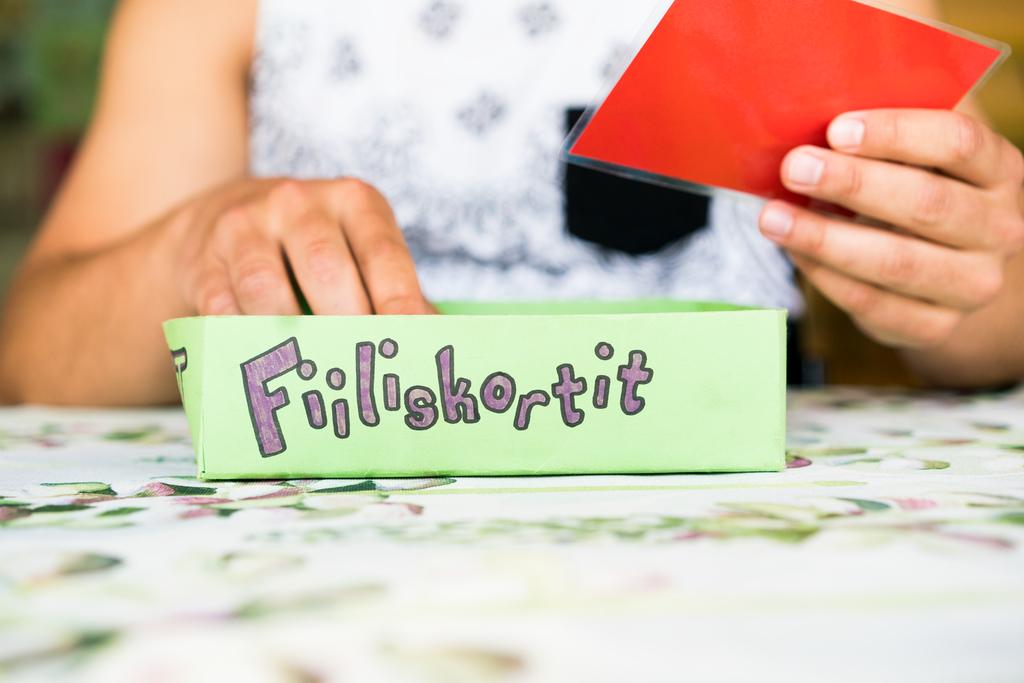 """Kuvassa nuori mies pitää punaista korttia kädessään. Edessä on kyltti, jossa lukee tunnetilaa kuvaava teksti """"Fiiliskortiti""""."""