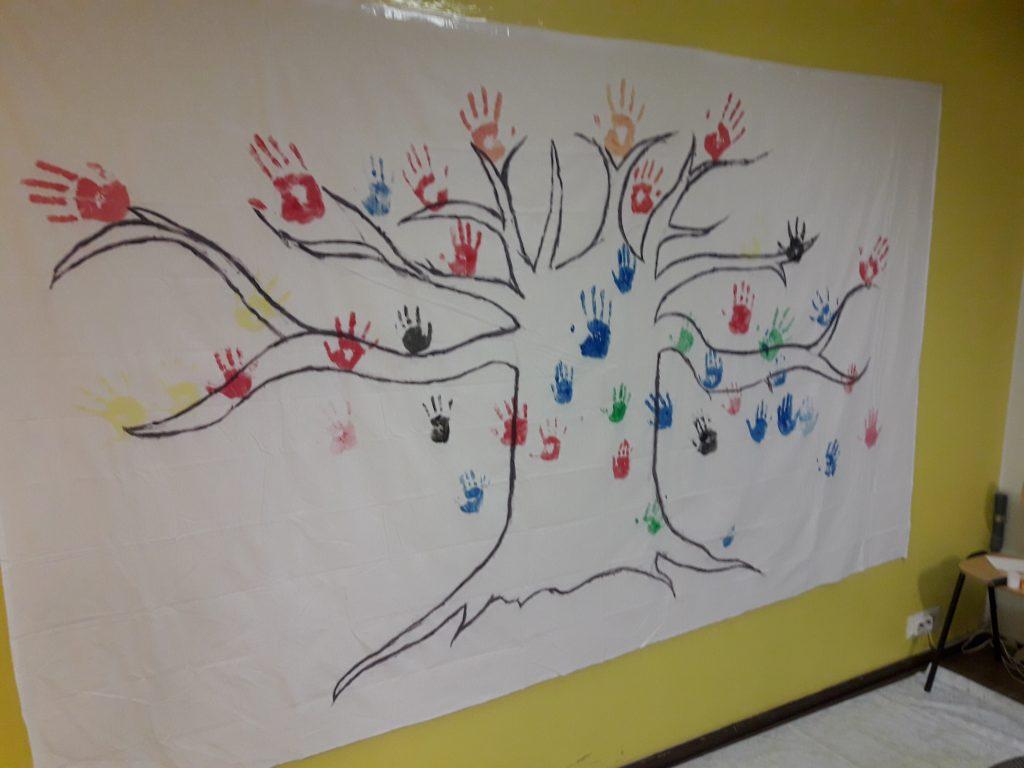 Seinävaate jossa puu ja kämmenten kuvia