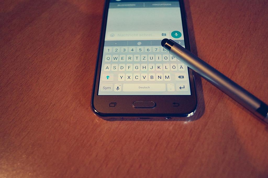 Matkapuhelin pöydällä ja sen päällä kynä