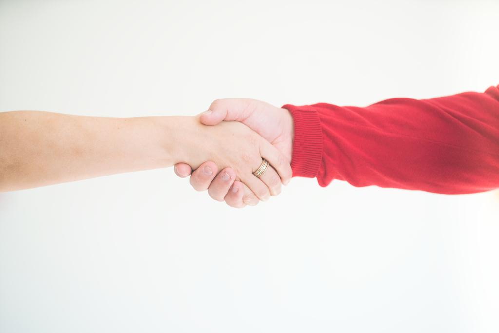 Kädenpuristus. Ehkä nuori työntekijä kättelee uutta esimiestään?