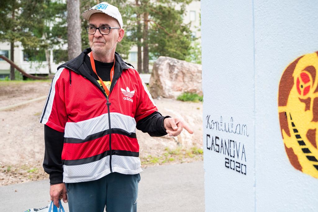 Kontulan D-asema: Mies osoittaa kädellään tekstiä muraalitaideteoksessa
