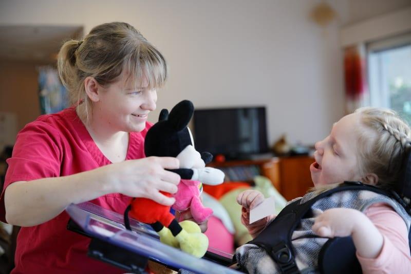 Lapsi- ja perhepalvelut yksikössä otettu kuva, jossa naisohjaaja näyttää Mikki Hiiri pehmolelua pyörätuolissa istuvalle hymyilevälle lapselle.