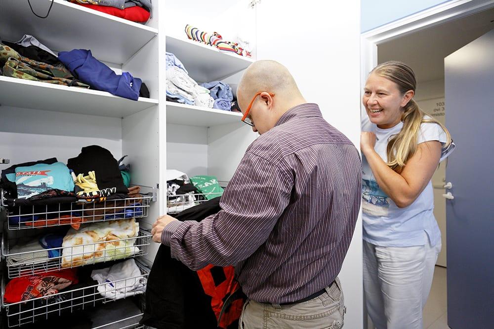 Ohjaaja opastaa miesasiakasta vaatteiden viikkaamisessa