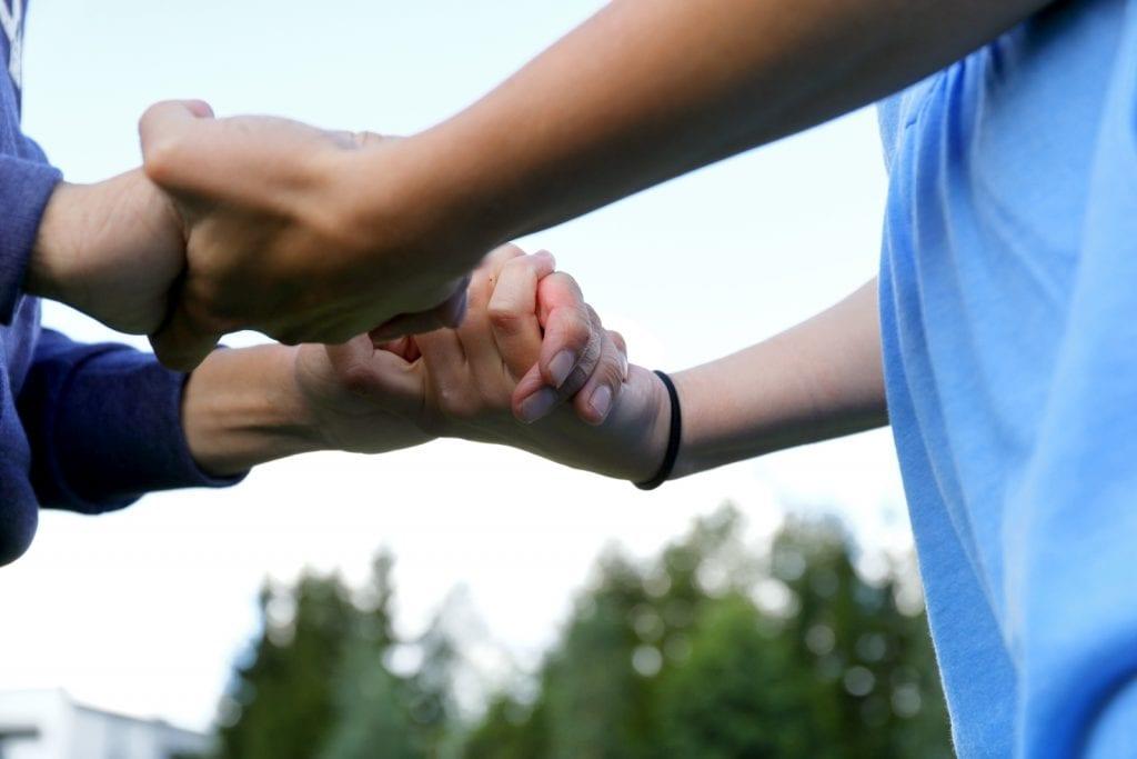 Kaksi henkilöä pitävät toisiaan kädestä kiinni