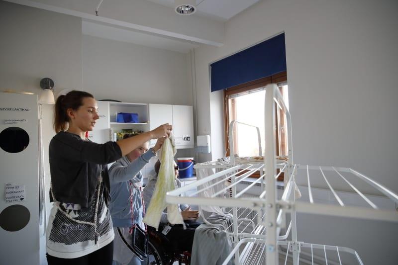 Ohjaaja ja asiakkaat ripustavat pyykkiä pyykkinarulle