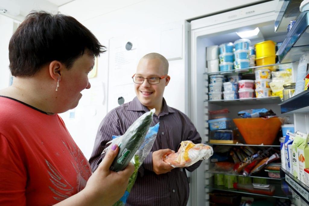 Kaksi asukasta jääkaapilla tutkimassa ruokia