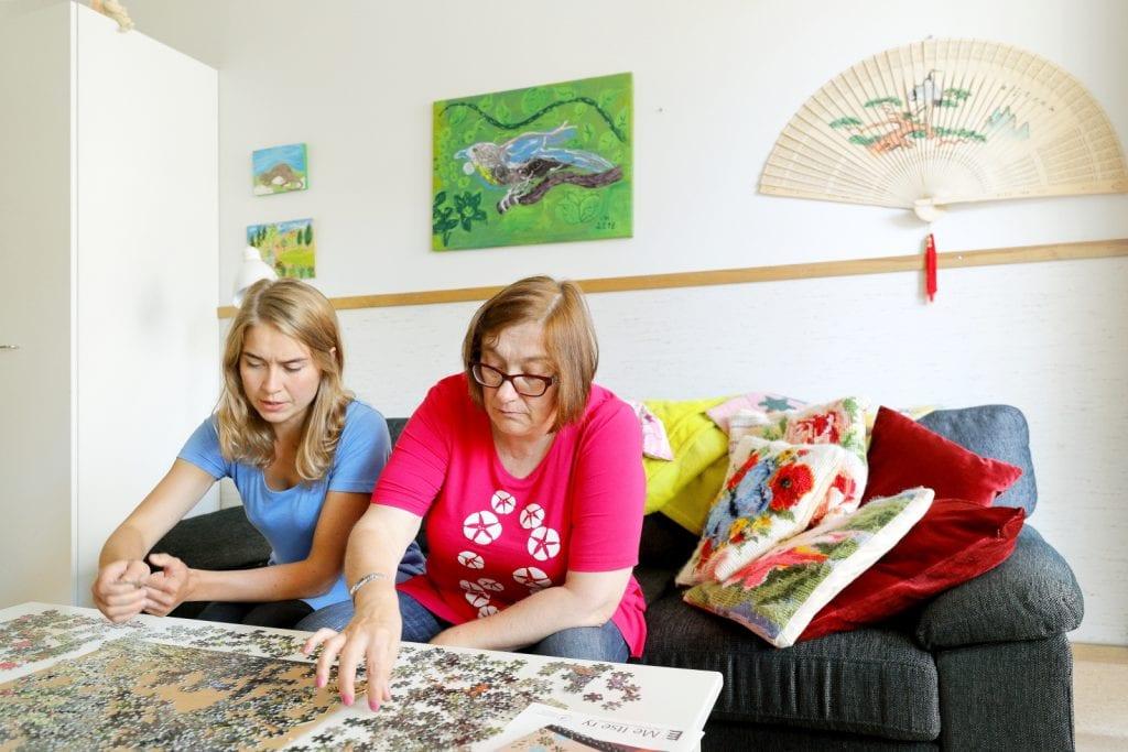 Asukas ja työntekijä tekevät palapeliä olohuoneessa