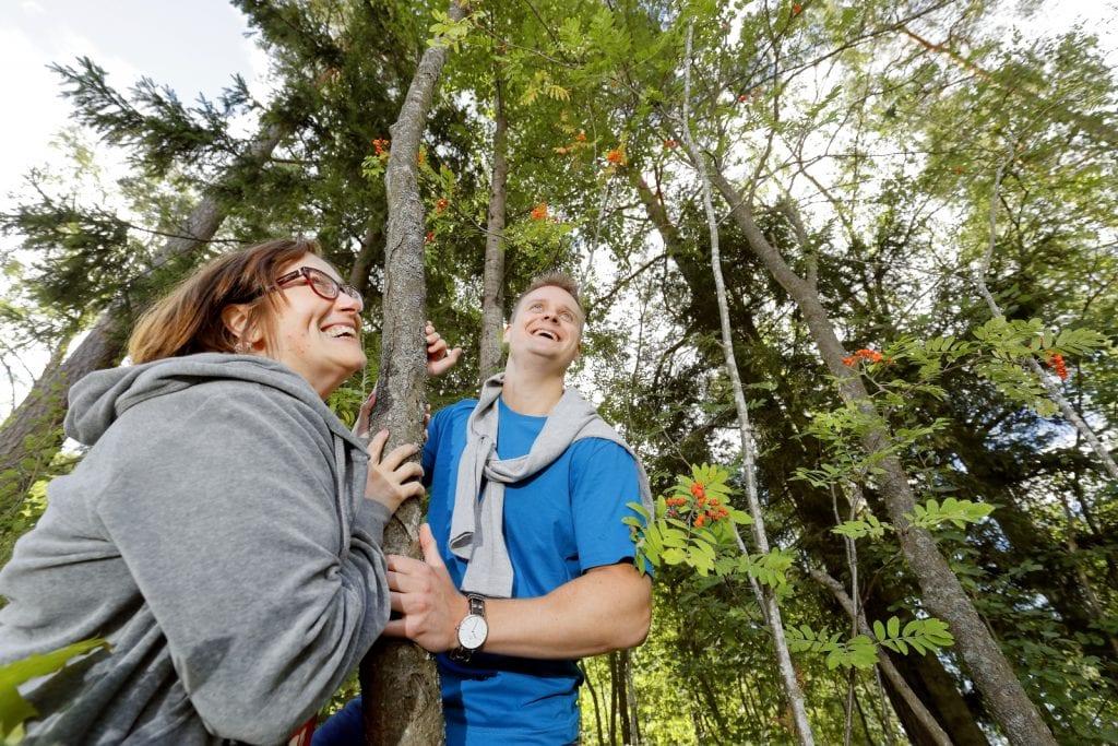 Asiakas ja hoitaja katsovat taivaalle puuhun nojaten