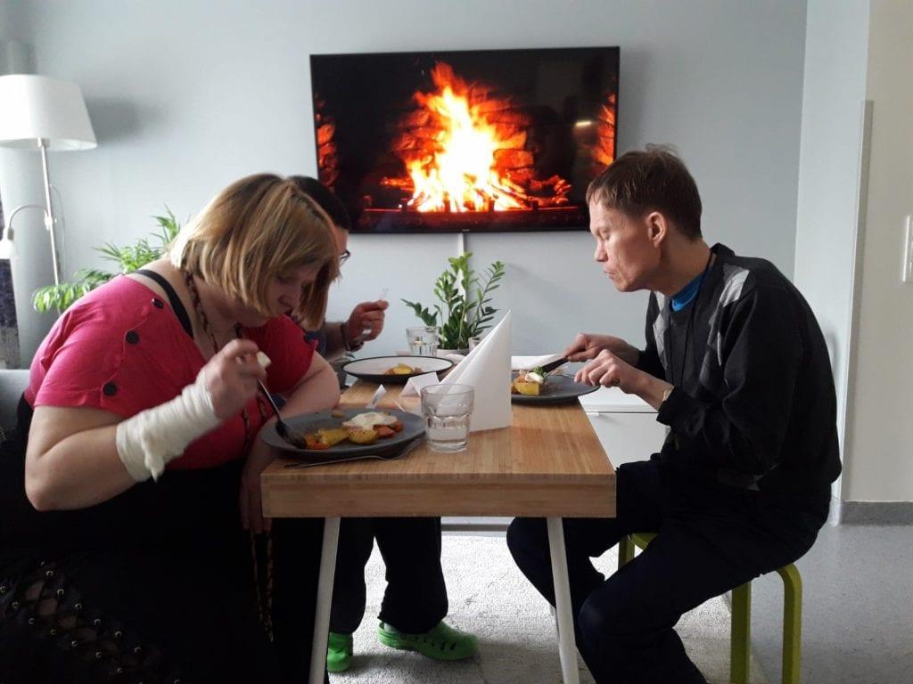 Paljerinteen asukkaita syömässä päivällistä keittiön pöydän ääressä