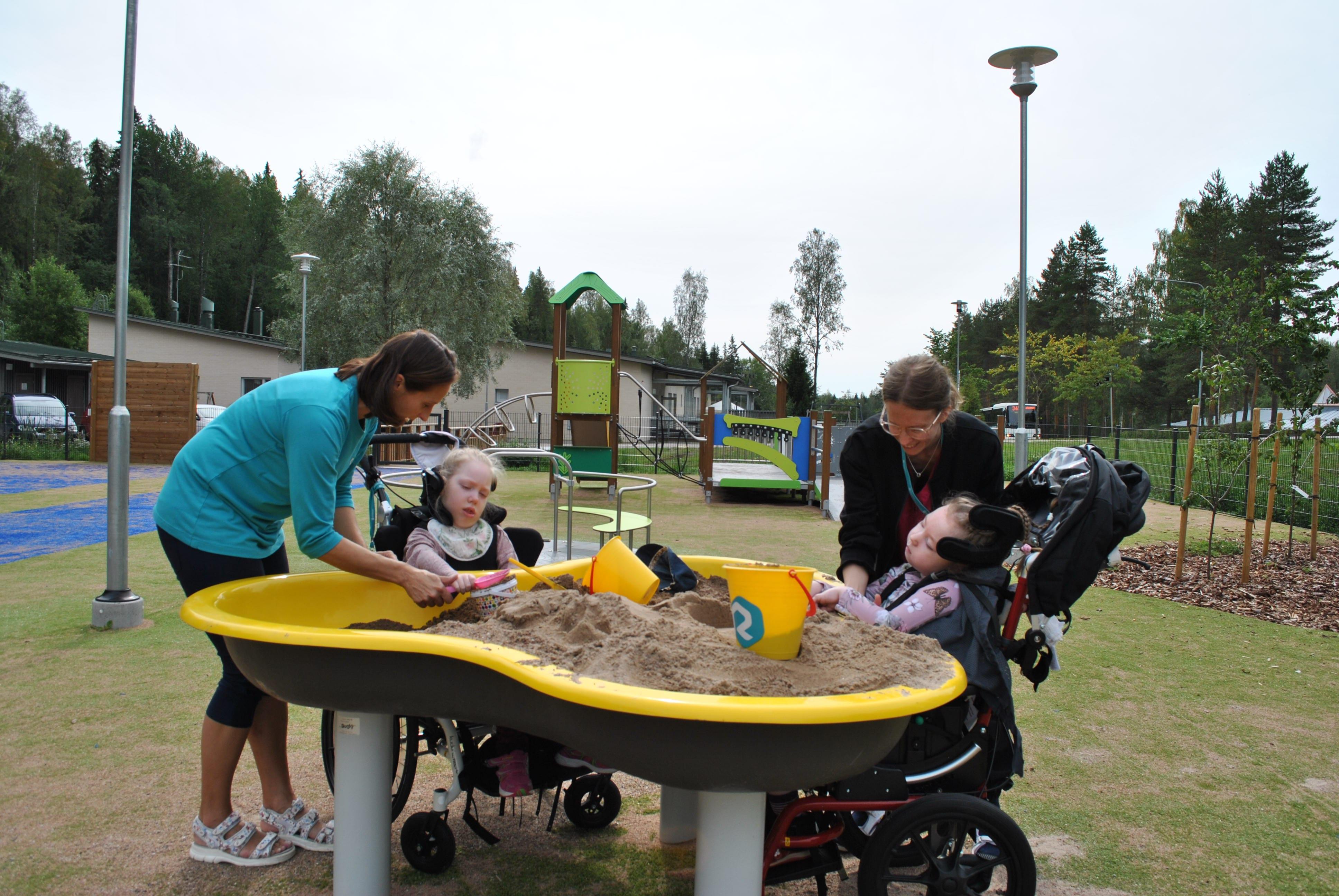 Kaksi kehitysvammaista lasta ja ohjaajat leikkivät esteettömällä hiekkalaatikolla ämpäreiden ja lapioiden kanssa