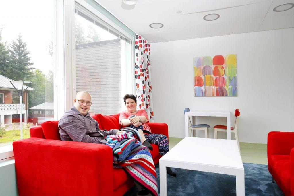 Kaksi asukasta istuu peiton alla punaisella sohvalla