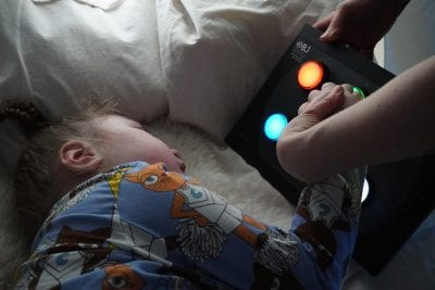 lapsi koskettaa eri värejä näyttävää valintapaneelia aistihuoneessa maaten