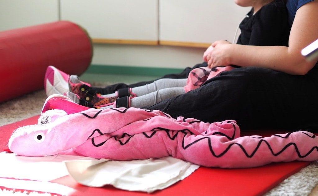 Maassa pinkki painokäärme ja lattialla ohjaaja lapsen kanssa aloittelemassa fysioterapiaa