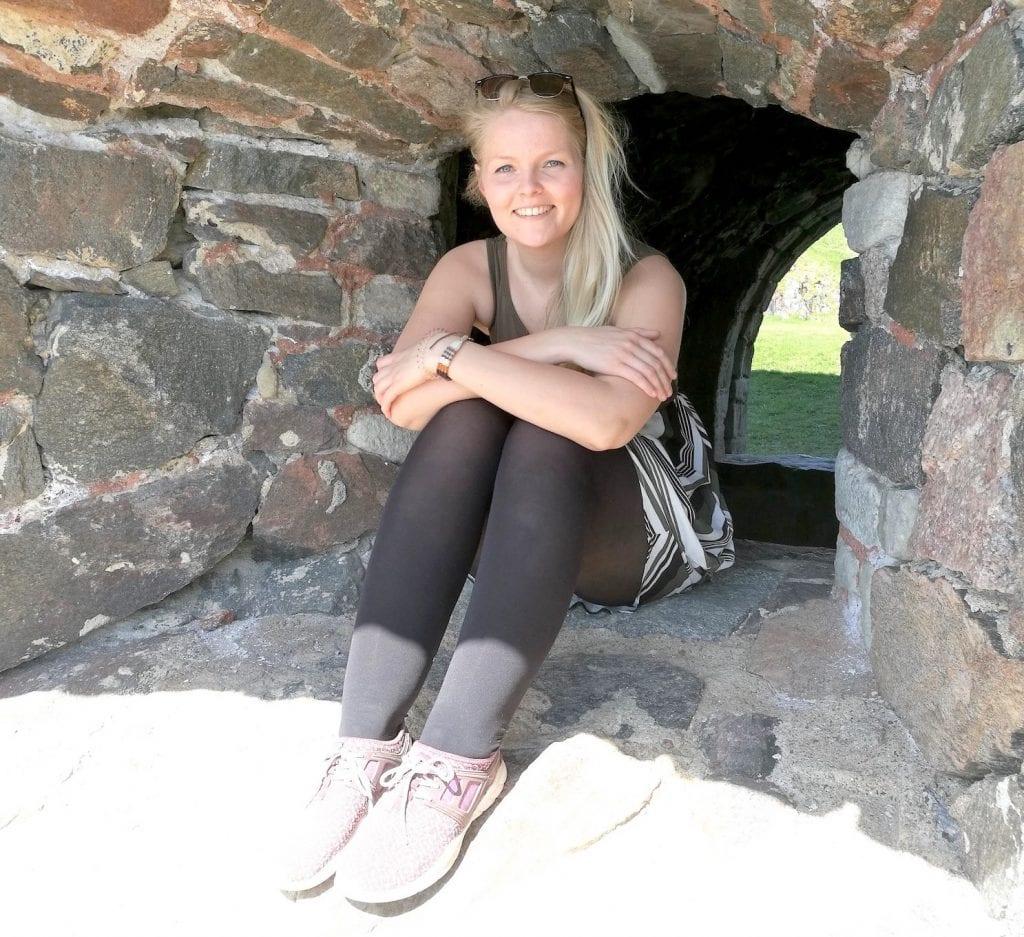 Sanna Niemi istuu kiviseinään upotetussa ikkuna-aukossa