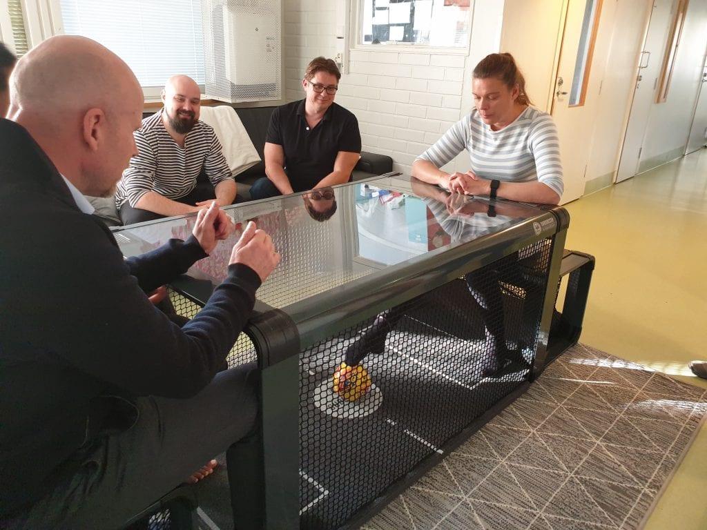Mira Paakko ja Jarmo Lonkola pelaavat Subseccer pöytäjalkapallopeliä Jarno Saarisen ja Markus Toivasen seuratessa vierestä sohvalla.