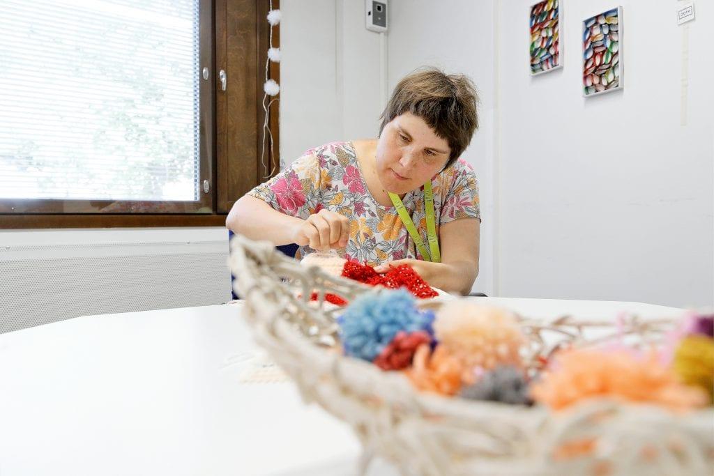 nainen tekee kädentöitä lankanaruista pöydän äärellä