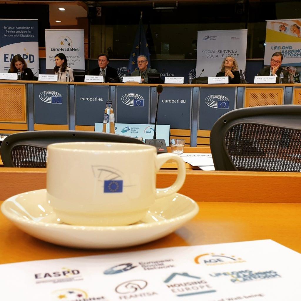 Kahvikuppi pöydällä ja taustalla näkyy paneelikeskusteluun osallistuneita henkilöitä