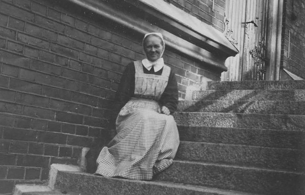Sisar Aino Miettinen istumassa portailla