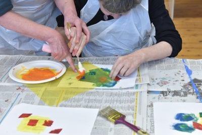 Kaksi henkilö maalaa paperille pöydän äärellä