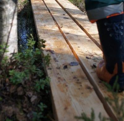 Pitkospuut, jolla seisoo henkilö kumisaappaat jalassa