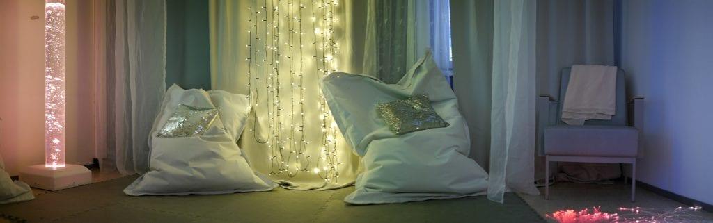 Aistiympäristö, jossa huoneessa säkkituoleja ja katosta roikkuvia valonauhoja