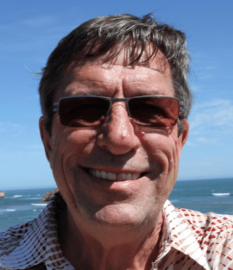 Aurinkolasipäinen Maurits Eijgendaal hymyilee, taustalla merenranta.