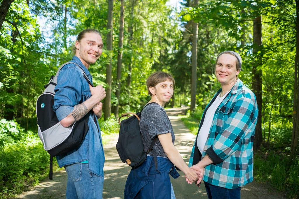 Kolme henkilöä seisoo metsäpolun varrella kameraan katsoen. Nainen ja mies pitävät käsistä kiinni, kolmannella henkilöllä on reppu selässään, jonka hihnasta pitää kiinni.