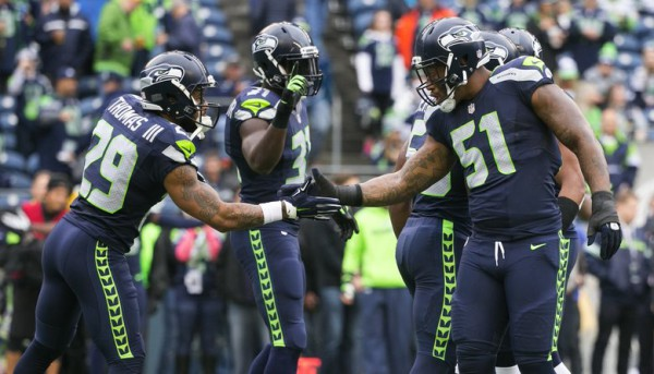 Seahawks linebacker Bruce Irvin, right, Seahawks safety Earl Thomas and Seahawks safety Kam Chancellor warm up before the Seattle Seahawks take on the Carolina Panthers at CenturyLink Field in Seattle Sunday, October 18, 2015.
