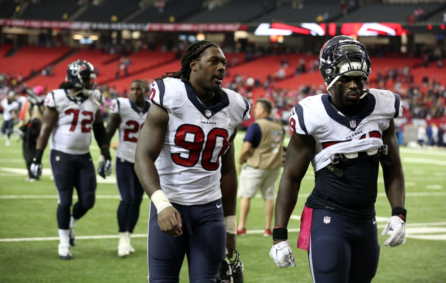 Oct 4, 2015; Atlanta, GA, USA; Houston Texans linebacker Jadeveon Clowney (90) and linebacker Whitney Mercilus (59) walk off of the field after their loss to the Atlanta Falcons at the Georgia Dome. The Falcons won 48-21. Mandatory Credit: Jason Getz-USA TODAY Sports