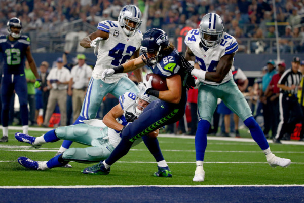 ARLINGTON, TX - NOVEMBER 1: Luke Willson #82 of the Seattle Seahawks takes the ball across the goal line to score a touchdown against Barry Church #42, Jeff Heath #38 and Morris Claiborne #24 of the Dallas Cowboys in the second quarter at AT&T Stadium on November 1, 2015 in Arlington, Texas. (Photo by Tom Pennington/Getty Images)
