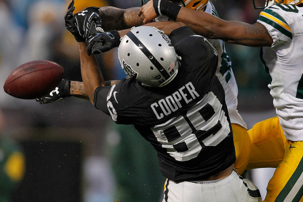 Oakland Raiders Amari Cooper (89) cannot hold onto the ball as he is defended by the Green Bay Packers Morgan Burnett (42), and Casey Hayward (29) in the fourth quarter of their NFL game at O.co Coliseum in Oakland, Calif, on Sunday, Dec. 20, 2015. (Aric Crabb/Bay Area News Group)