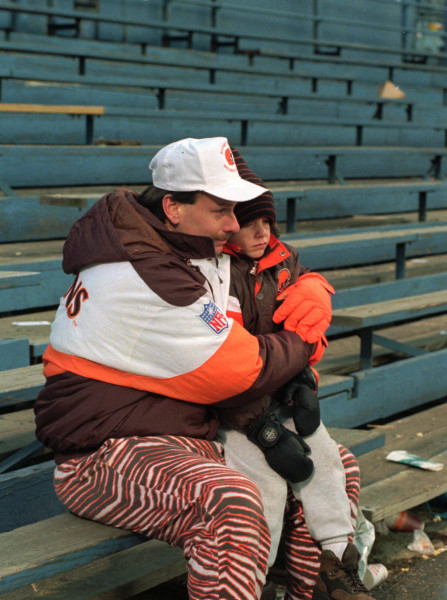 Joe Shapaka holds his six-year-old son, Matthew, at their seats in the bleachers at Cleveland Stadium after the Browns-Cincinnati Bengals game which may have been the final Cleveland Browns game there Sunday, Dec. 17, 1995. (AP Photo/Jeff Glidden)